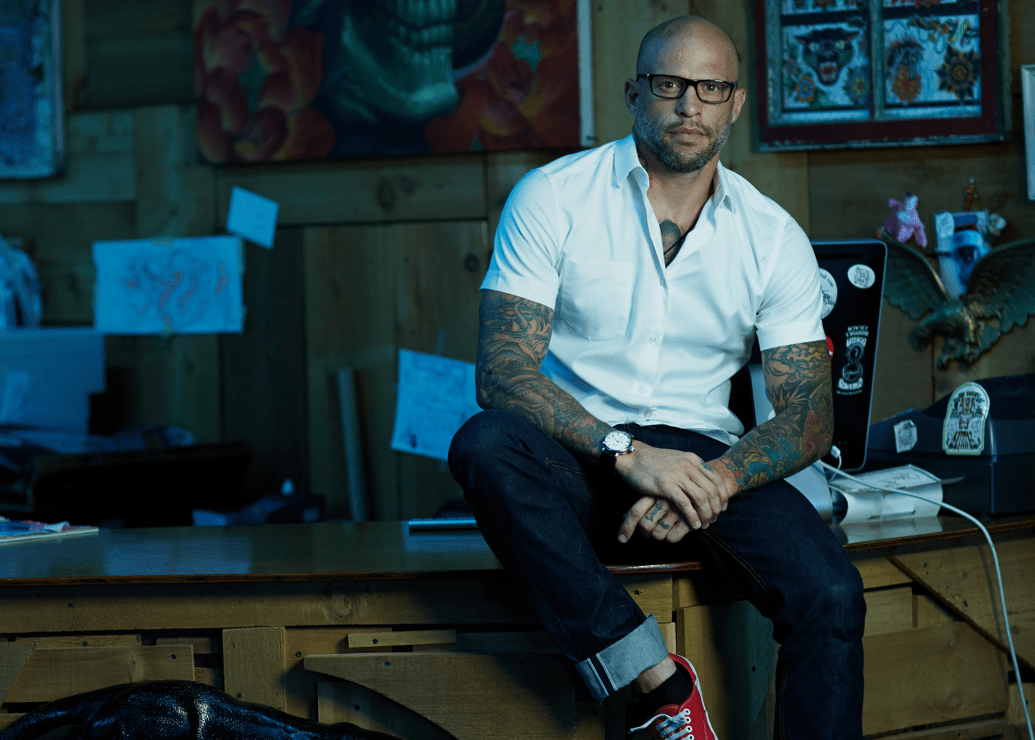 Ami James sitting on a desk