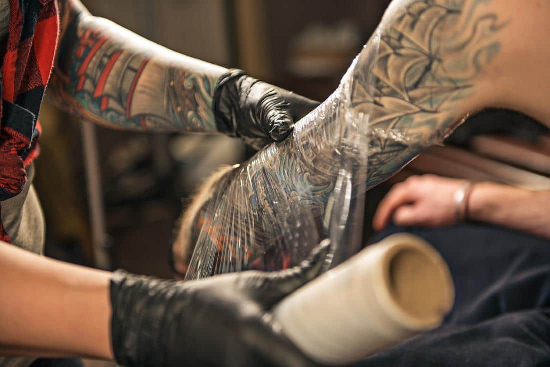 Your tattoo artist will wrap your new tattoo at the shop, which will protect it from dangerous bacteria entering your vulnerable skin in the first few days.
